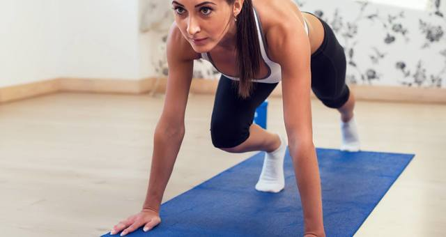 Woman on Blue Yoga Mat in Plank Pose